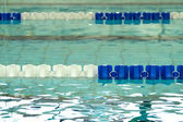 Empty swimming pool with blue and white lane dividers — Stock Photo