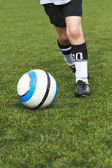 Youth player running after a soccer ball — Stock Photo