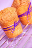 Muffin with purple ribbon — Stock Photo
