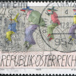 A stamp printed in Austria, represented Carnival Figures Riding High Bicycles, by Paul Flora, circa 1985 — Stock Photo
