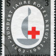 Royalty-Free Stock Photo: A stamp printed in the Austrian, is dedicated to the 100th anniversary of the International Red Cross emblem, circa 1963