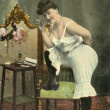 Vintage postcard, depicts a woman in pantaloons and a cigarette, circa 1908 - Stock Photo