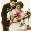 German postcard. Depicts a man and a woman, Easter eggs and a bouquet of beautiful flowers, circa 1923. Text in French: Christ is Risen! - Stock Photo