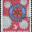 Постер, плакат: LUXEMBOURG CIRCA 1965: A stamp printed in Luxembourg is dedicated to the 60th anniversary of Rotary International shows Rotary Emblem and Cogwheels circa 1965