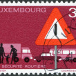 Stock Photo: LUXEMBOURG - CIRC1970: stamp printed in Luxembourg, is dedicated to importance of road safety shows Traffic Sign and Street Scene, circ1970