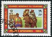 Un sello impreso en el afganistán dedicada al día mundial del turismo. representado conductor camello, carpa, camello en jaez, circa 1984 — Foto de Stock