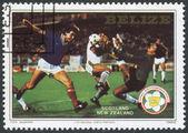 Um selo impresso do belize, dedica-se à fifa world cup 1982, na espanha, mostra uma partida entre escócia - nova zelândia, por volta de 1982 — Foto Stock