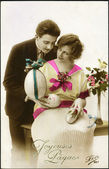 German postcard. Depicts a man and a woman, Easter eggs and a bouquet of beautiful flowers, circa 1923. Text in French: Christ is Risen! — Stock Photo