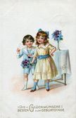 "German postcard greeting, ""Congratulations to Birthday!"", depicts a boy and a girl with flowers, circa 1916 — Stock Photo"