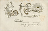 "German greeting postcard ""I heartily congratulate with New Year!"", depicts the sun, flowers and a horseshoe, circa 1905 — Stock Photo"