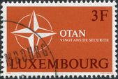 LUXEMBOURG - CIRCA 1969: A stamp printed in Luxembourg, is dedicated to 20th anniversary of the North Atlantic Treaty Organization or NATO, shows the symbol NATO — Stock Photo