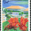 Stock Photo: Stamp printed in Japan, prefecture Okinawa, depicts conference center Bankoku Shinryokand flowering Erythrinvariegata, circ2000