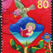 A stamp printed in Japan, dedicated to the International Day of Children's Books, shows a girl sitting in a flower and reads a book, circa 2000 — Stock Photo #12162906