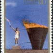 A stamp printed in Japan, dedicated to the 50th Postwar Memorial Year, shows the lighting of the Olympic torch Yoshinori Sakai, Tokyo 1964 — Stock Photo #12163024