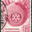 A stamp printed in Australia, is dedicated to the 50th anniversary of Rotary International, shows the Globe, Flags and Rotary Emblem - Stock Photo