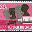 A stamp printed in the Indonesia, is dedicated to Five-year Development Plan. Family and hypodermic syringe, circa 1969 - Stock Photo
