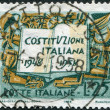 Foto Stock: A stamp printed in Italy, is dedicated to the 10th anniversary of the Constitution shows Book and Symbols of Labor Industry and Agriculture
