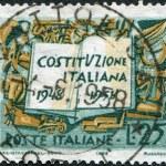en stämpel tryckt i Italien, är tillägnad tioårsdagen av konstitutionen visar boken och symboler av arbetskraft industri och jordbruk — Stockfoto