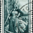 A stamp printed in Italy, shows Girl worker in hemp field, in the background Pomposa Abbey (Emilia-Romagna), circa 1950 - Stock Photo