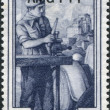 A stamp printed in Italy, shows the Auto mechanic, in the background Sacra di San Michele, Florence, (Piedmont), (overprint AMG FTT) - Stock Photo