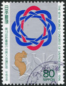 A stamp printed in Japan, is dedicated to the 18th Congress of Savings Banks, shows the emblem of the Congress and squirrel, circa 1996 — Stock Photo
