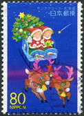 A stamp printed in Japan, the prefecture Hokkaido, depicts children in a sleigh of Santa Claus, circa 1999 — Stock Photo
