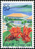 A stamp printed in Japan, prefecture Okinawa, depicts a conference center Bankoku Shinryokan and flowering Erythrina variegata, circa 2000 — Stock Photo