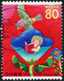 A stamp printed in Japan, dedicated to the International Day of Children's Books, shows a girl sitting in a flower and reads a book, circa 2000 — Stock Photo