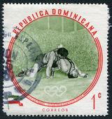 En stämpel som tryckt i dominikanska republiken, olympisk mästare sholam takhti, iran, lightweight brottning, ca 1960 — Stockfoto