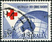 A stamp printed in Australia, dedicated to 40th anniversary of the Australian Red Cross, represented the Red Cross and Globe, circa 1954 — Stock Photo