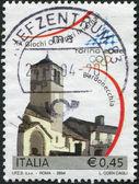 Eine briefmarke gedruckt in italien, ist spezielle winter olympics, turin, zeigt kirche san pietro apostolo, bardonecchia, 2004 — Stockfoto