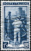 A stamp printed in Italy, shows Shipbuilding, in the background Rapallo Castle (Liguria), circa 1950 — Stock Photo
