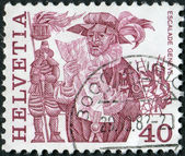 SWITZERLAND - CIRCA 1977: A stamp printed in Switzerland, is depicted Herald reading proclamation and men scaling wall, Geneva, circa 1977 — Stock Photo