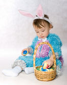 A small child dressed as a rabbit, basket and Easter eggs. — Stock Photo