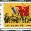 ROMANIA - CIRCA 1974: A stamp printed in the Romania, dedicated to 30th anniversary of Romania's liberation from Fascist rule, shows the Romanians and Flags, circa 1 - Stock Photo