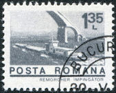 ROMANIA - CIRCA 1974: A stamp printed in the Romania, shows the tugboat on the Danube river goes under the bridge, circa 1974 — Stock Photo