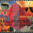 NETHERLANDS - CIRCA 1997: A stamp printed in the Netherlands, shows Amaryllis surrounded by cup of coffee, two glasses of wine, hand writing card, candlelight, circa — Stock Photo