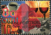 NETHERLANDS - CIRCA 1997: A stamp printed in the Netherlands, shows Amaryllis surrounded by cup of coffee, two glasses of wine, hand writing card, candlelight, circa — 图库照片
