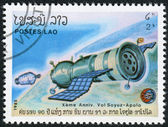 LAOS-CIRCA 1985: A stamp printed in the Laos, depicts the spacecraft Soyuz approaching Apollo, circa 1985 — Stock Photo