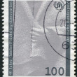 A stamp printed in Germany, dedicated to 40th anniversary of the Geneva Convention on Refugees, shows a hand holding cloak and emblem — Stock Photo