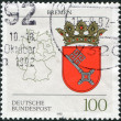 A stamp printed in Germany, shows the coat of arms of the Federal Land Bremen and the German map — Stock Photo