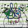 Royalty-Free Stock Photo: A stamp printed in Germany, is dedicated to the 125th anniversary of German Choral Society, shows musical notes, treble clef, leaves
