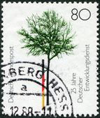 A stamp printed in Germany, dedicated to 25th anniversary of the German Volunteer Service, shows a young tree — Stock Photo