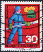 A stamp printed in Germany, shows a fireman to extinguish the fire — Stock Photo