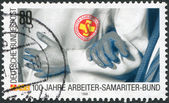 A stamp printed in Germany, is dedicated to the 100th anniversary of the Samaritan Association of Workers Rescue Service — Stock Photo