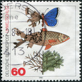 A stamp printed in Germany, is dedicated to protecting the environment, shows a butterfly, fish, and a branch with injuries from a bad environment — Stock Photo