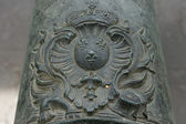 French coat of arms of King Louis XIV (Sun King) on the old bronze cannon. — Stock Photo
