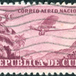 Stock Photo: CUB- CIRC1932: postage stamp printed in Cuba, shows airplane Ford 4-AT (Tin Goose) over mountain landscape, circ1932