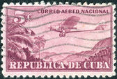 CUBA - CIRCA 1932: A postage stamp printed in Cuba, shows a airplane Ford 4-AT (The Tin Goose) over mountain landscape, circa 1932 — Stock Photo