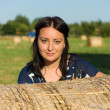 A woman and a stack of straw — Stockfoto